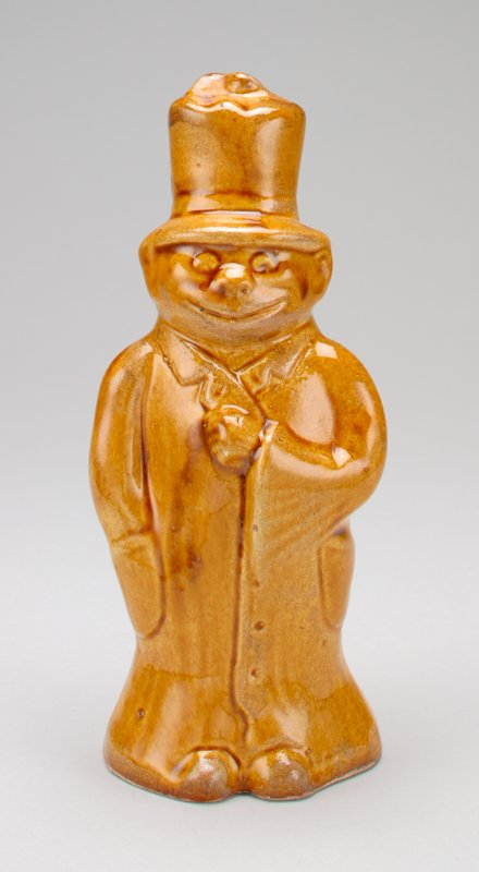 "mustard gold figure of a standing man; wearing a long coat to the floor and a very high top hat; smiling; PR hand in his pocket; coin slot down the back; bottom stamped with a double eagle and ""1198"""