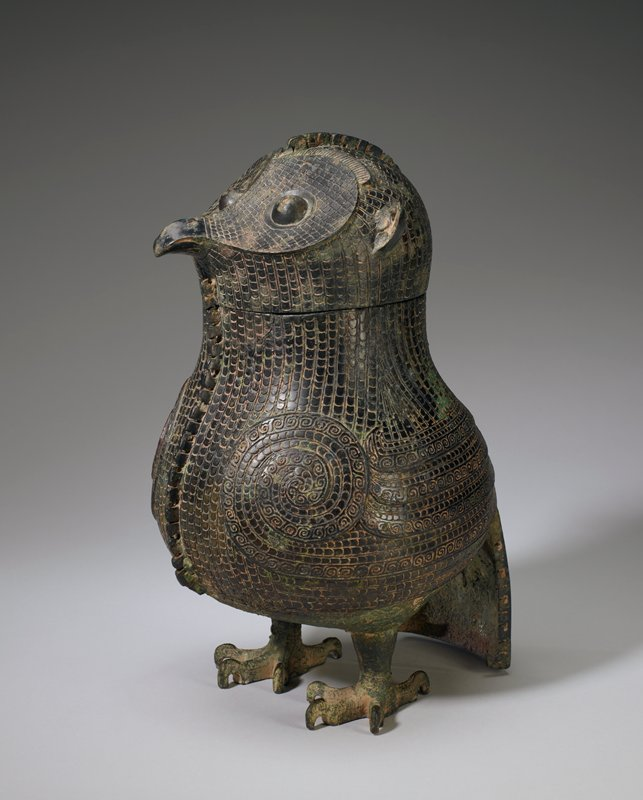 Vessel in the shape of an owl. Two flanges, one ending just under the beak in front and the other continuing to the top of the head in back, have alternating straight and L-shaped scores, those on the front flange being much the deeper of the two. The tail, with a scored flange border, forms the back support of the vessel. Apart from the realistically-formed feet, the bird is strongly stylized. The body is completely covered by rows of scales except for the shoulder line, expressed by a vigorous spiral, and the wings quills, rendered by bands filled with antithetical spirals. Patina green.