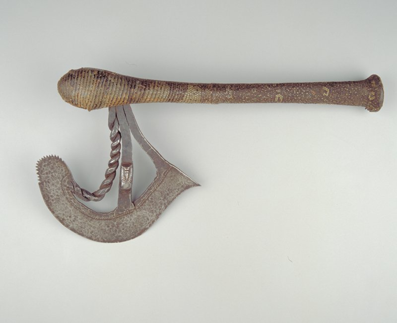 long handle covered with snake skin, curved blade with face near center