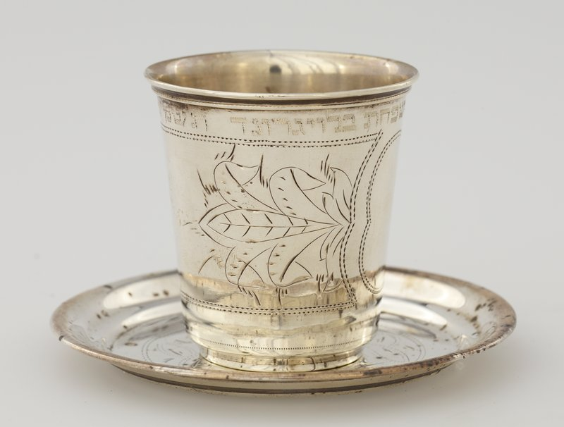 small tumbler-style cup; band with organic designs and central cartouche; text above; saucer has organic designs flanking a shield, inside a circle