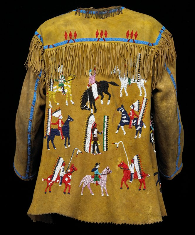tanned hide body with pinked hem; fringe around sleeves, at top back and at shoulders; military braid around neck and top of button placket; multicolored beaded designs of warriors and rodeo scenes