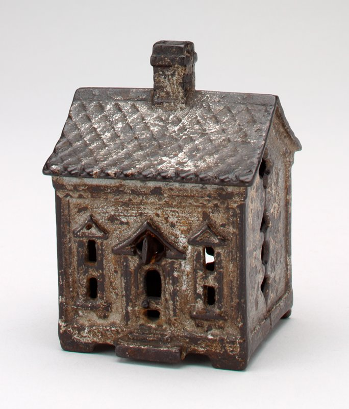 small silver block-shaped building; door and 2 windows in front; 2 windows and coin slot in back; chimney on roof