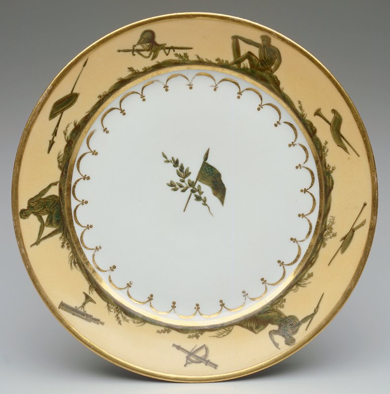 Cream rim background; porcelain dinner plate, gold rim and band at interior; rim decorated by landscape scene; seated classical figures and symbols; American flag with 13 stars at center