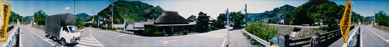 413 degree panoramic color photograph; intersecting roads with tile-roofed house at center; small white truck at left; old woman at right; yellow banner with black characters visible at left and right