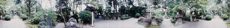 412 degree panoramic color photograph; garden with paved paths and small shrine structures; stone statue right of center