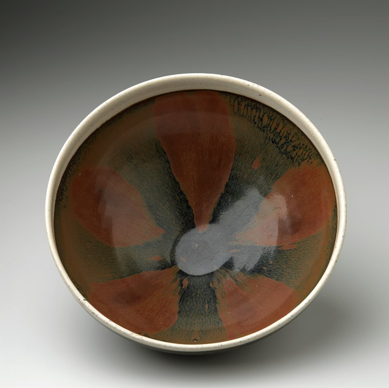small foot; wide flaring sides; rust brown glaze with splashed black drips on exterior and radiating stripes on interior; white rim