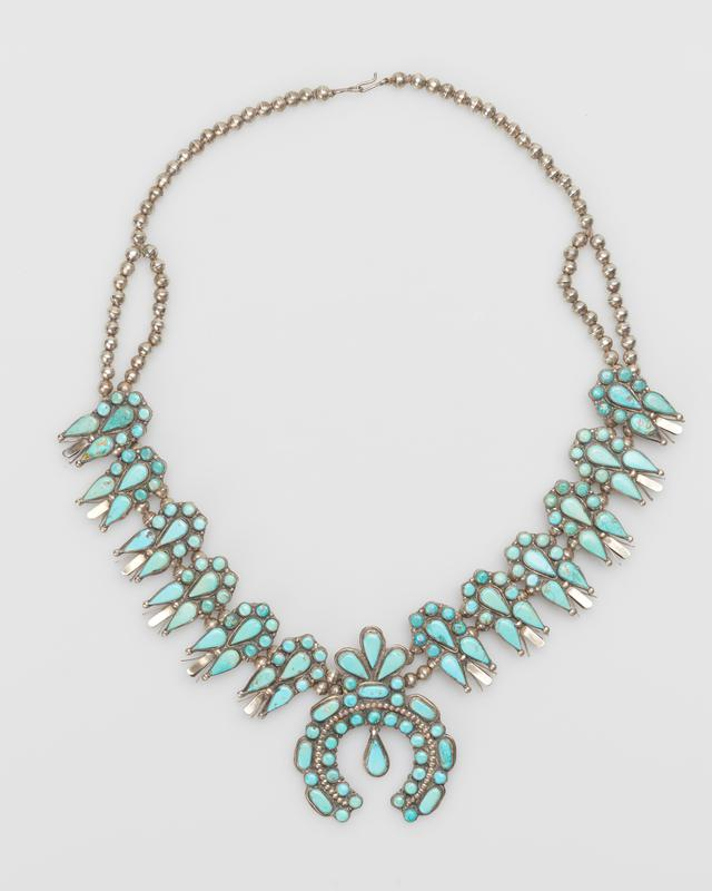 Double strand of spherical silver beads; twelve squash blossoms overlaid with large clusters of round and pear-shaped Stennich turquoises; sheet naja set with round elliptical and pear-shaped Stennich turquoises, center pendant, serrated bezels; filed bezels indicate Zuni work; J.#394, Cat.#435.