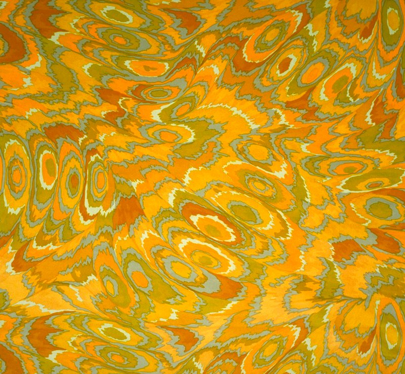 """Peacock-like swirling design. Handprinted cotton velvet. Vertical repeat 40"""". Cotton velvet Hand Print. Amber, gold, yellow, grey oval designs & vertical wavy lines. 40"""" repeat. Amber"""