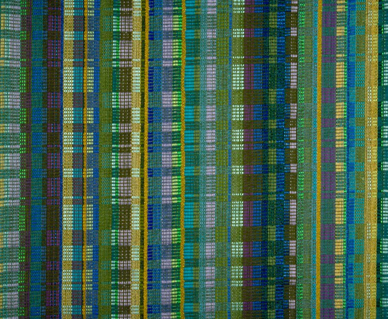 """""""Woven complex of many yarns in all fibers. Vibrant, solid, rich with vigor."""" Mixed warp Uph. 27 different yarns. Handwoven. Some color metallics, stripes and blocks of many colors, blue, green, brown, purple, gold Spice Fire Blue"""