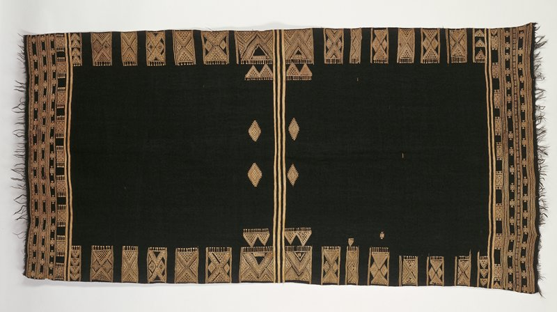 black with tan design; stripes down center, blocks of triangles and diamonds top and bottom, bands of stripes and designs next to fringed sleeve edges