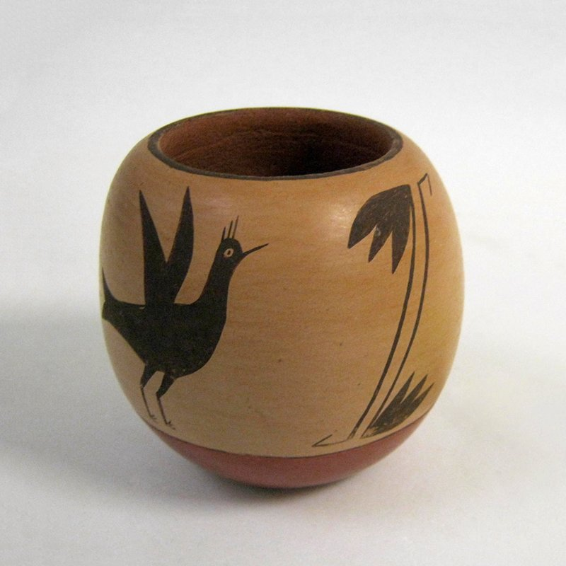 small rounded vessel; decorated with 2 birds and 2 pair of organic designs in brown on tan; brown mouth; red at bottom