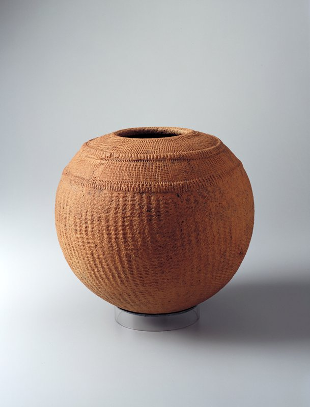 round ceramic vessel which imitates a round woven basket; two raised bands at upper shoulder; mouth opening of 4-3/4 inch
