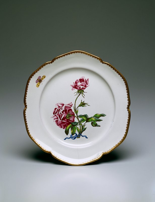 Six-lobed faience plate, with decorative gilding on rim; a solid line of gilt, with groups of three strokes pointing inward; center contains spray of two blossoming roses, with one unopened bud, tied together with a blue ribbon; along the edge appears one butterfly or moth, with yellow and pale lavender wings; roses in carmine purple