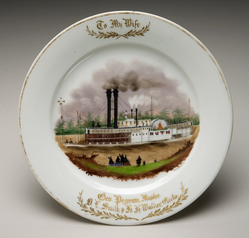 """plate decorated with enamel and gilding: design of steamboat """"Ruth""""; 4 figures on boat; 7 figures on shore, one fishing; gold text and leaf sprays at rim"""