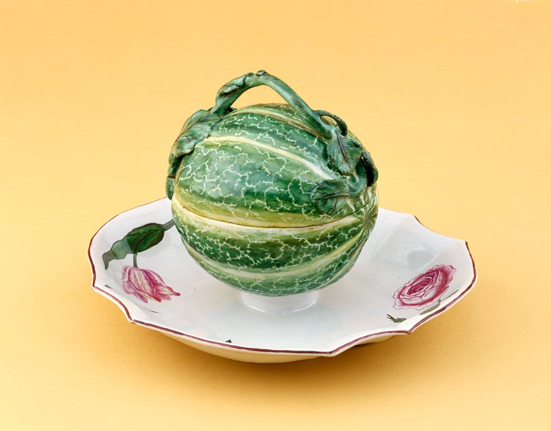 covered faience bowl in shape of a melon; vine and leaves forming handle; bottom half is attached to a lobed platter with flowers (rose and tulip at either end)