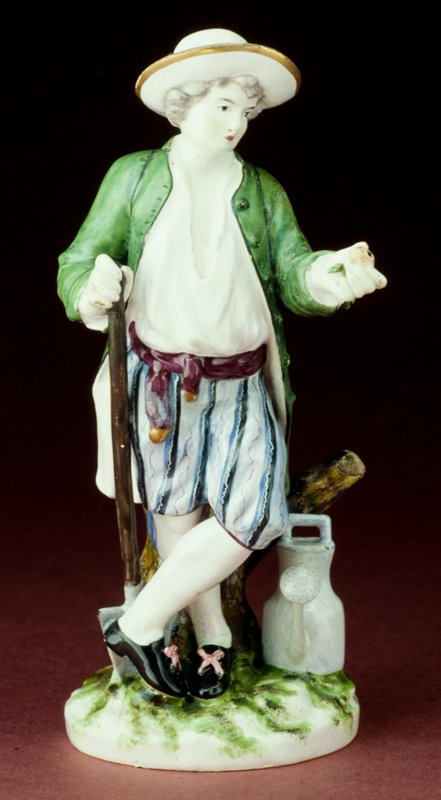 faience figure of a gardener boy supported by a tree stump and leaning on a shovel; wearing a green coat; holding an apple in his right hand; with a watering can at his feet