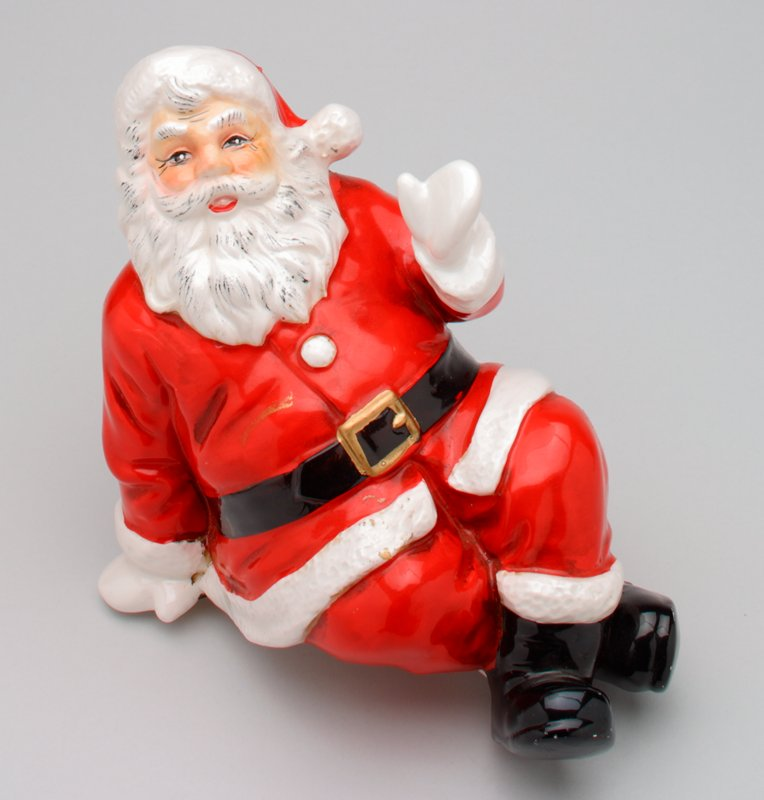 seated Santa Claus figure, made to sit with legs hanging from ledge; smiling Santa waves with PL hand; feet crossed