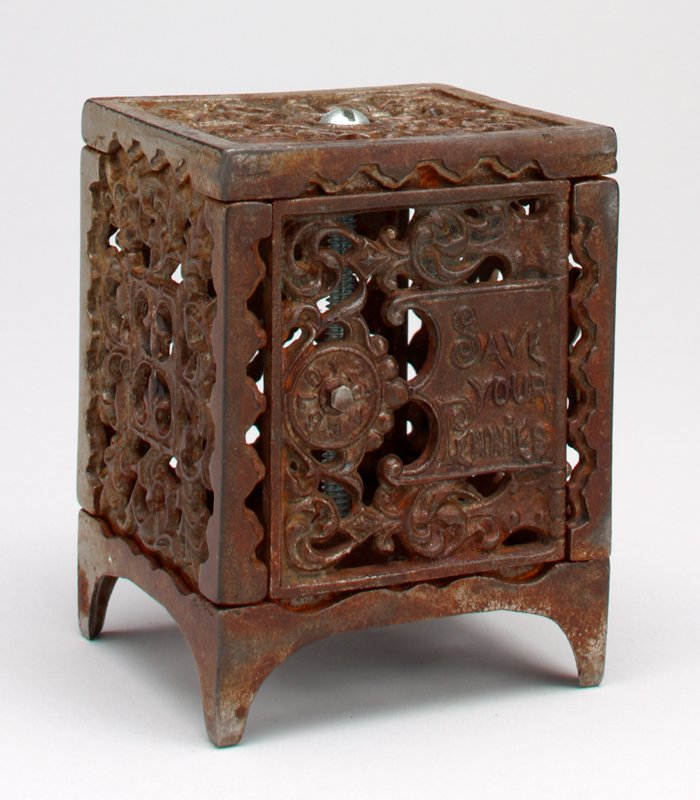 "openwork combination safe with imitation dial on front, left; ""SAVE YOUR PENNIES"" on front, right; scrolls and geometric openwork designs overall"