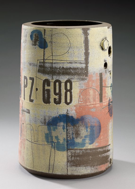 cylindrical vessel on flat foot; inward-flaring, flat mouth ring; brown glaze at interior and bottom; six circular cut-outs and two circular protrusions; letters, numbers, lines and blotches of color in brown, pink, yellow and white on body