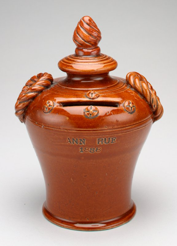 "brown ceramic urn shaped bank with rope like handles and a bud like top; Four small decorative knots next to coin slot; ""Ann Rue 1888"" stamped on front;"