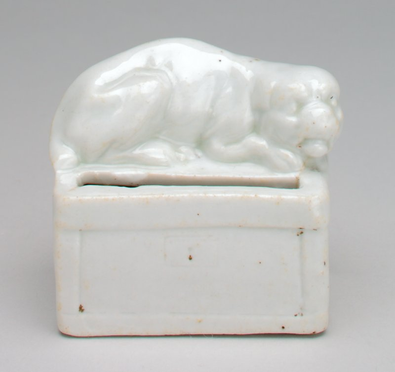 shiny glazed white dog sleeping on a box with a coin slot on the top of the box in front of the dog;