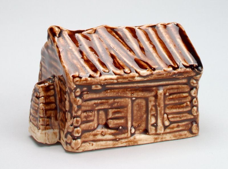 ceramic log cabin with shiny glaze; door and window on front, coin slot at back;