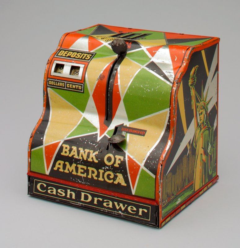 metal multicolored bank in the form of cash register for dimes, nickels and quarters; 2 sliding levers on front and 2 windows recording deposits in dollars and cents; on one side the Statue of Liberty on the other children in a bank; key missing