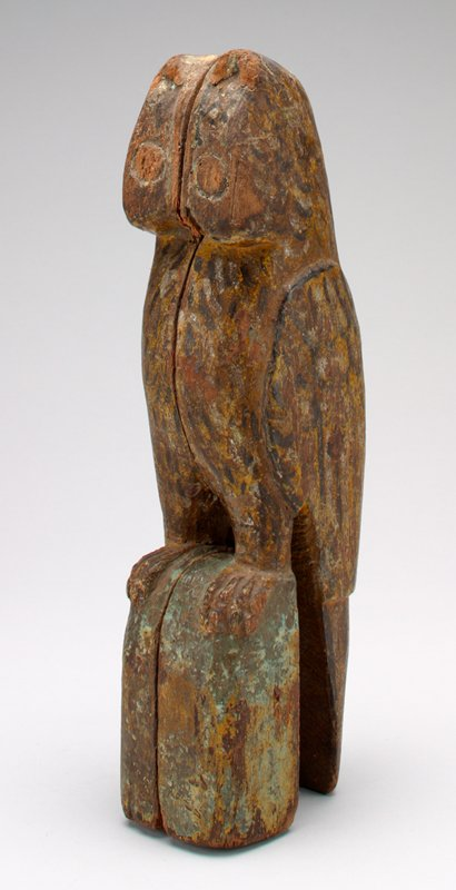 2 pieces hand carved wood in shape of owl perched on a stump- pegs for eyes; traces of brown, yellow, green and red pigment; coin slot back of head
