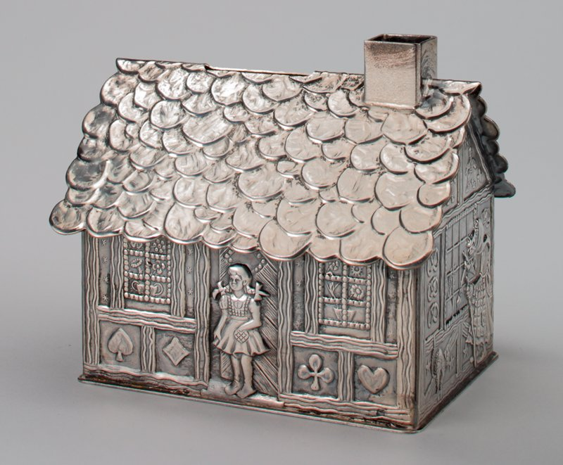 silver color house; Gretal in doorway; Hansel and witch on ends; pretzles, gingerbread people, cat and other designs on sides; coin slot in roof