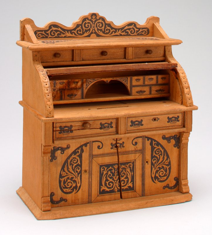 roll top desk with drawers, doors and deccorative designs painted on in black; coin slot on desk top at center; keyhole on back