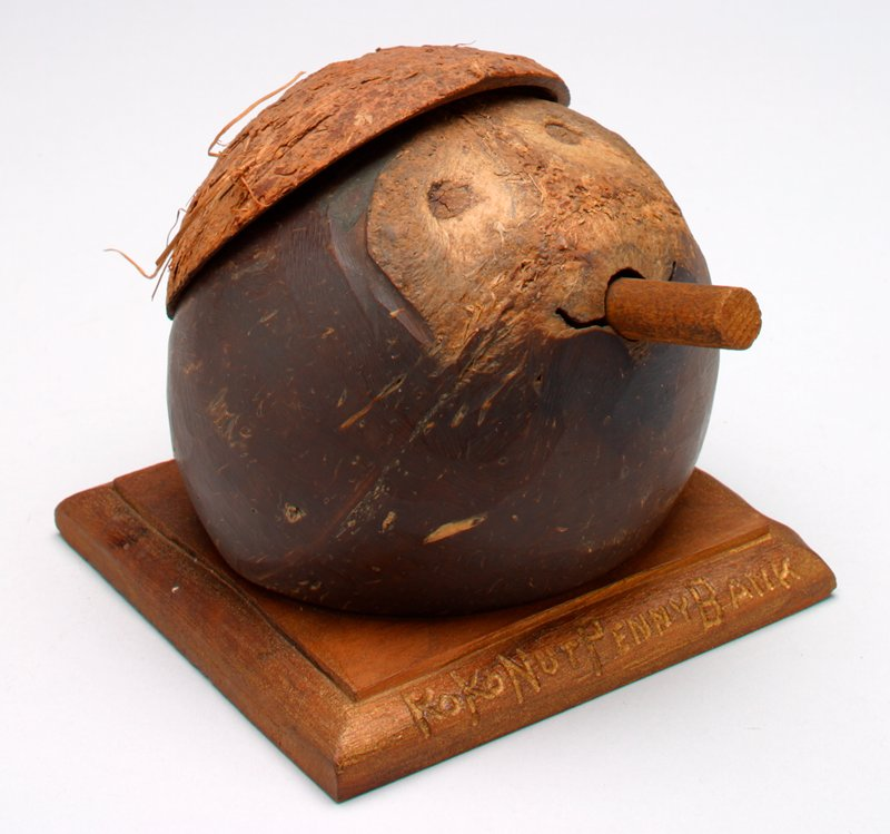 "brown wood partial sphere set on square wood base; face with stick in mouth; coin slot under ""hair"""