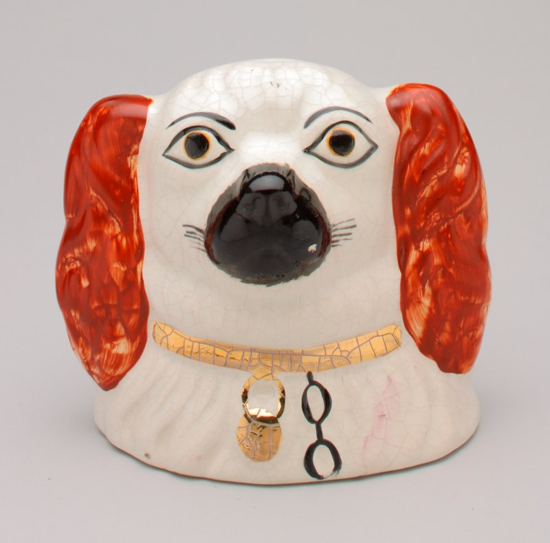 Staffordshire-style dog's head; black muzzle; red ears; gold collar with black chain; coin slot at top of head; shiny glaze finish
