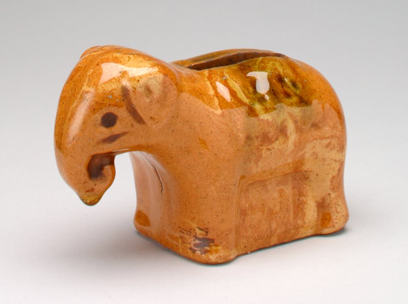 brown ceramic elephant; standing; trunk down curled into mouth; coin slot in back