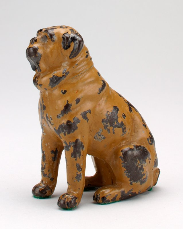 tan seated dog with short curled tail; bag(?) tied around neck; coin slot in back