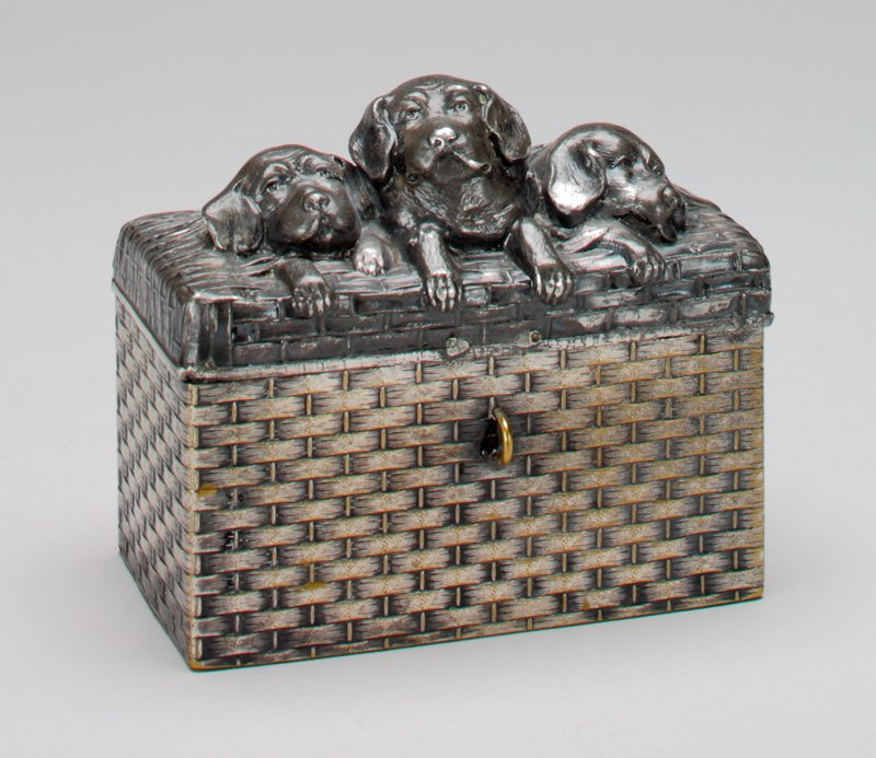 "silver plated rectangular basket with opening cover; 3 puppies in the basket; hallmark on the bottom; small card-shaped sign in one corner of top with ""Express"" printed on it; loop on front"