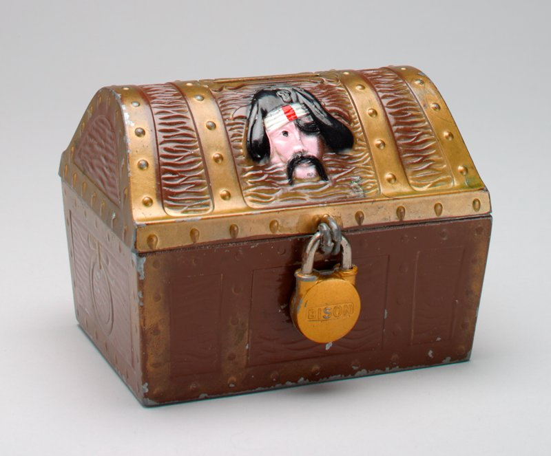 metal pirate chest with lock on front; picture of pirate on one side of top and skeleton on other side of top; brown with gold bands around; 2 keys taped to bottom