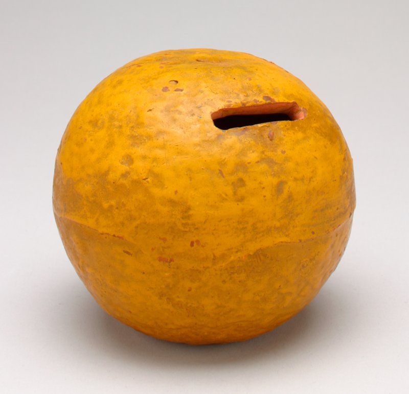 molded and painted to resemble an orange; has a small hole where stem should be; coin slot in side