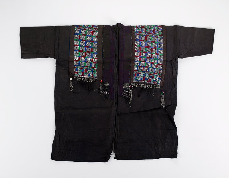 dark indigo dyed; short sleeves; decorated on chest, shoulders and back with small pieces of silver metal and geometric embroidery in primarily green, maroon and purple