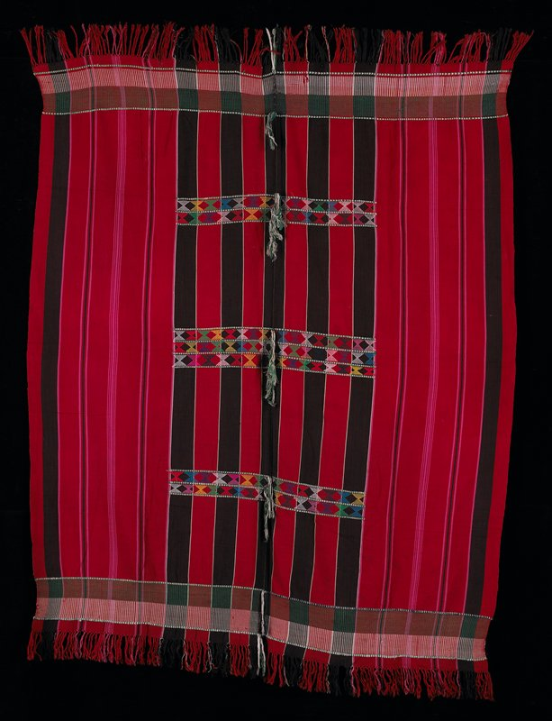 """striped red blanket with knotted fringe at two ends; stripes are black and pink; stitched 4"""" wide bands at both ends with fringe; bands are green and white; seven central bands, approximately 18"""" long, of multicolored stitching in an X pattern in center of blanket"""