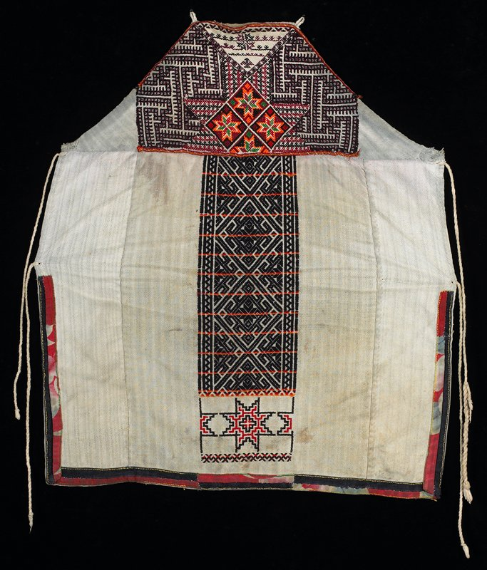 white body embroidered with geometric and star patterns, predominately in blue and purple; red printed and blue fabric trim