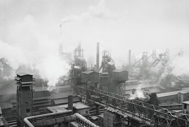 industrial complex from above- buildings, smoke stacks and smoke; long platform of steel girders in foreground, LR corner to center foreground
