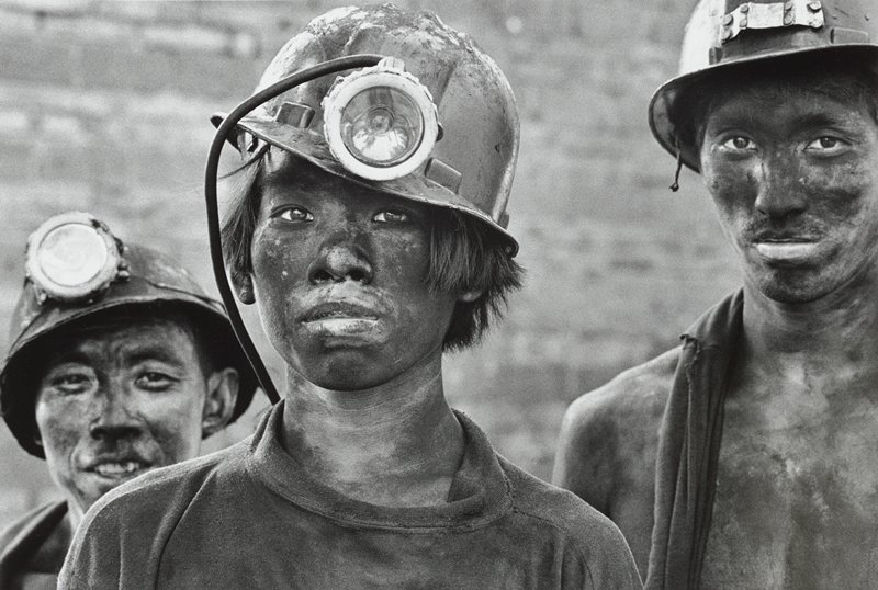 three young men with soot on their faces, wearing hard hats with miner's lamps