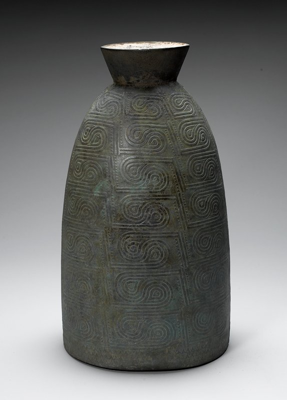 ovoid body, tapering at top with outward-flaring top section; relief design with teardrop shapes, swirls and zigzags; greenish patina