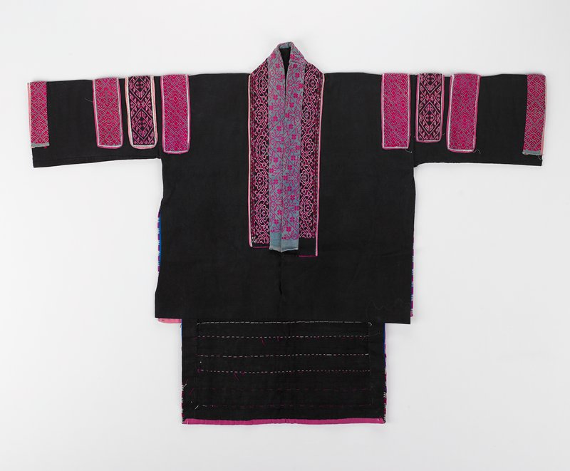 "black open front; cotton; 8-1/2"" tail; neckline has blue denim with pink floral cross stitch and black band with pink and white geometric cross stitch trim; four bnads from shoulder to cuff of satin and cross stitch on same; back has elaborate swirl in pink, green and white, framed; tail is rows of applique embroidered as the front"