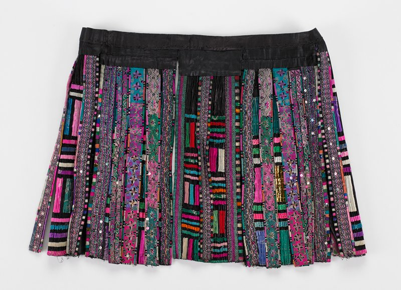 """base fabric of pounded indigo; 2 1/2 to 3"""" waistband with 2 ties; 7 crimped, alternating 6"""" and 4"""" panels plus 11 overlaying 1""""panels; wider panels are narrowly crimped and tacked together; applied ribbon decoration in pinks, reds, blues, greens yellows and white; narrow panels are embroidered in geometric and floral designs with sequins and metallic thread in many colors; very complex and colorful"""