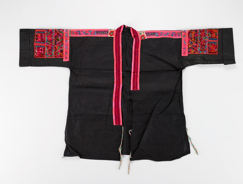"""pounded indigo jacket with side vents; shocking pink and red edging up front and around neck 2""""wide; 2 tape ties on front and on vents; shoulders and sleeve panels heavily embroidered with very imaginative and very colorful fauna including birds, tigers and fish; PR sleeve has tape label with numbers"""