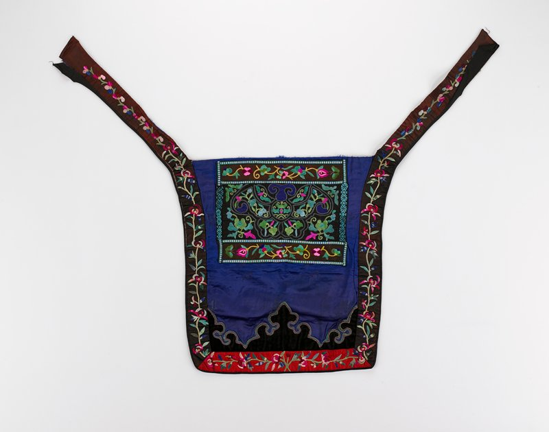 blue damask body with rectangle in top center with flat embroidery of flora in green, pink, blue on brown silk; ties form border on three sides in red and brown with padded embroidered flora; black velvet applique with scroll corners outlined in green and pink braid with gold metallic; lined in red chrysanthemum print