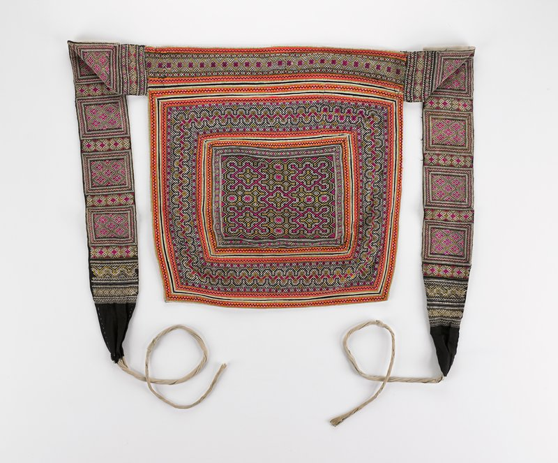 "3-1/2"" waistband with attached 4-1/2"" wide embroidered ties; top and bottom covered with geometric motifs overall; central rectangle in lower section in 11"" x 13"" with unusual ""molecule"" design; several rows of stitched applique around all designs; pink, orange, yellow, green on black; grey lining"