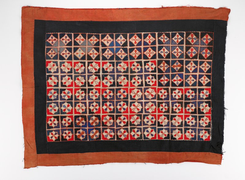 outer red border on three sides; inner blue border surrounding many square sections of four appliqued squares with looped center design in red and blue on white; couched thread surrounds each applique; squares are similar but not identical; unlined