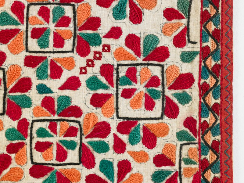 """red, green, tans floral embroidery--some in black embroidered squares; black, green, tan triangular 1/2"""" border bound in red; white lining"""
